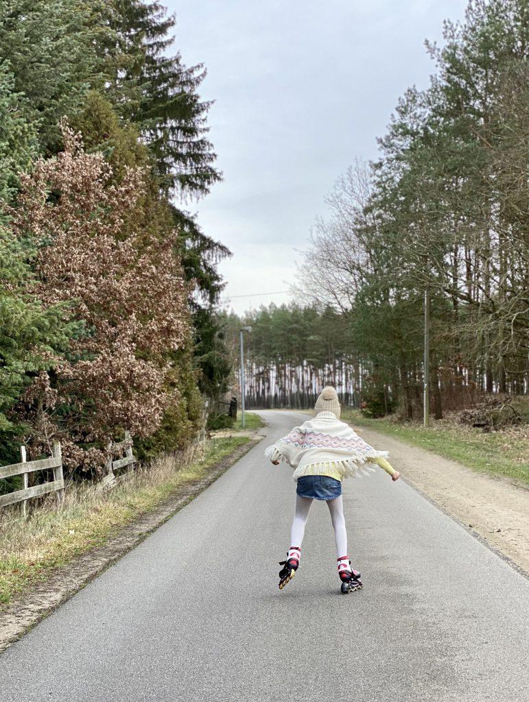 Kind fährt auf Landstraße Inliner
