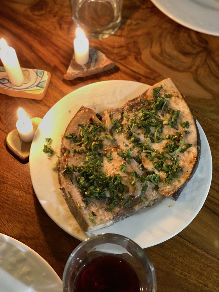 gebratener Schwertfisch auf weißem Teller mit Minze bestreut und Kerzen daneben