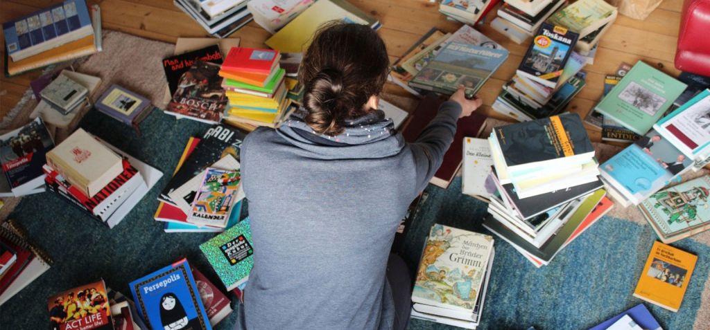 Mädchen von oben, die von Büchern umgeben ist. Sie sortiert und ordnet seeoffensichtlich. Ausmisten ist auch eine Fasten-Idee.