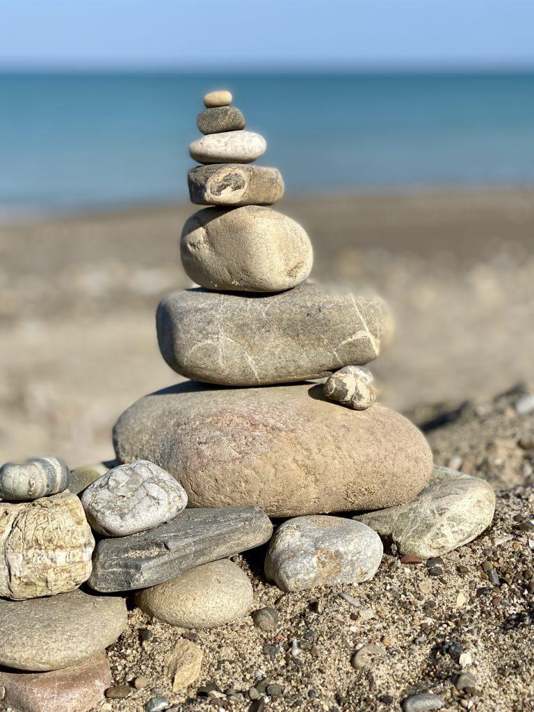 Steinpyramide am Strand vor Meer