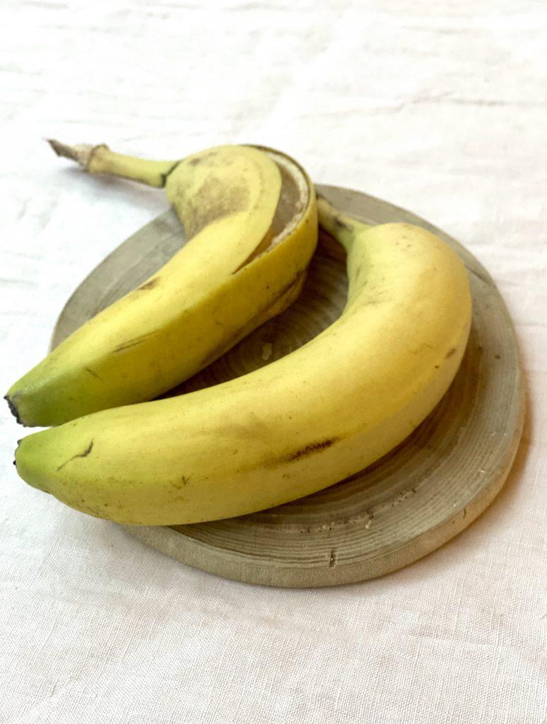 2 Bananen auf einem runden Holzbrettchen