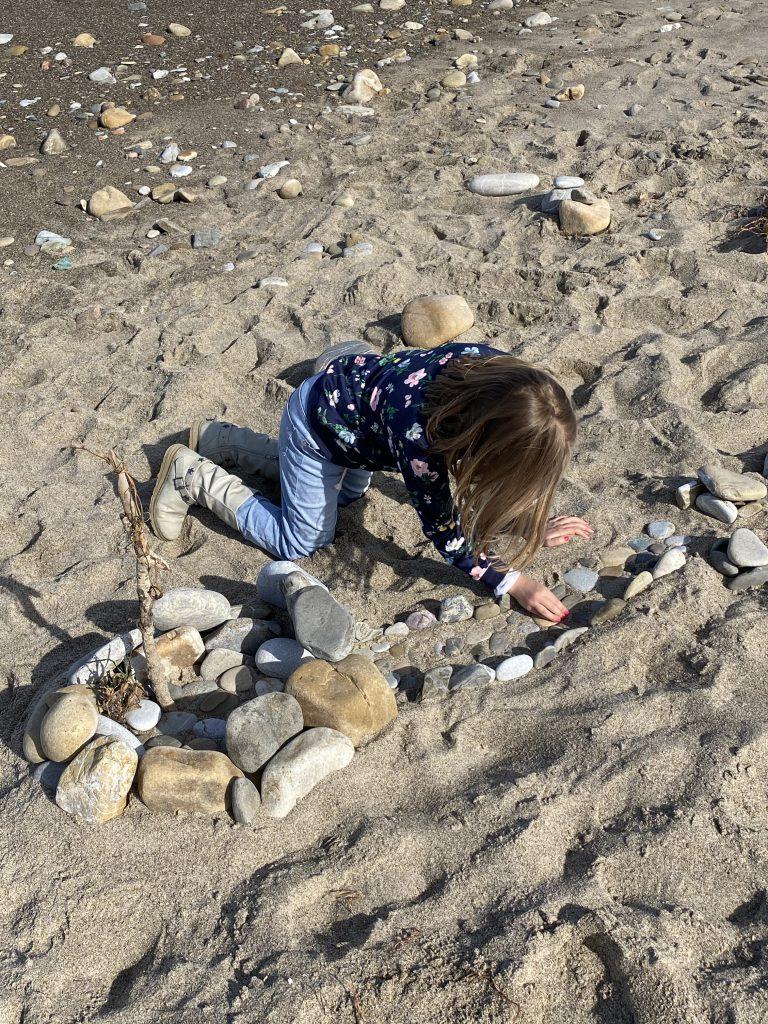 Kind spielt im Sand mit Strinen
