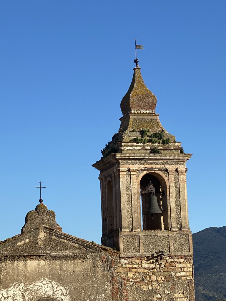 Kirchturm mit Glocke vor blauem Himmel