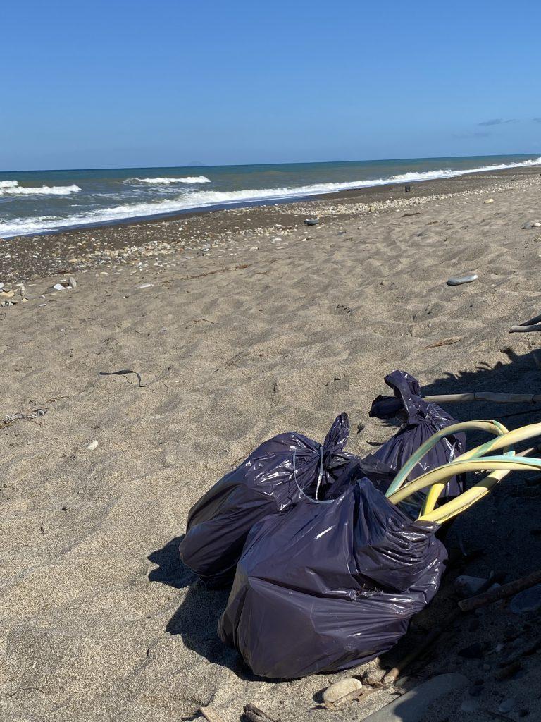 3 Müllbeutel gefüllt liegen am Strand