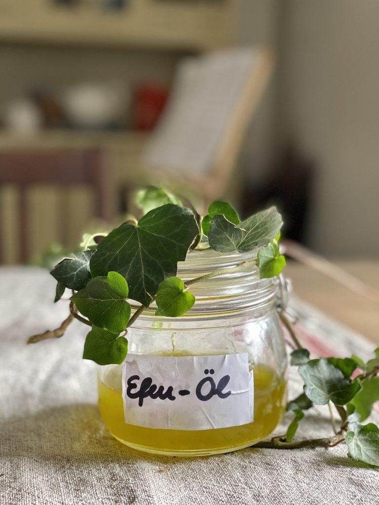 Peeling selber machen: Glas mit Efeu-Öl auf dem Tisch. Das braucht man für das Peeling.