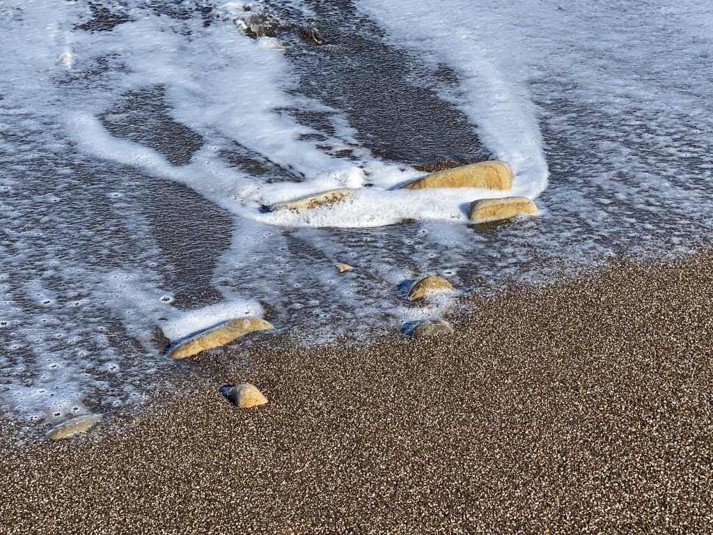 Wasser fließt an Steinen vorbei auf Sand