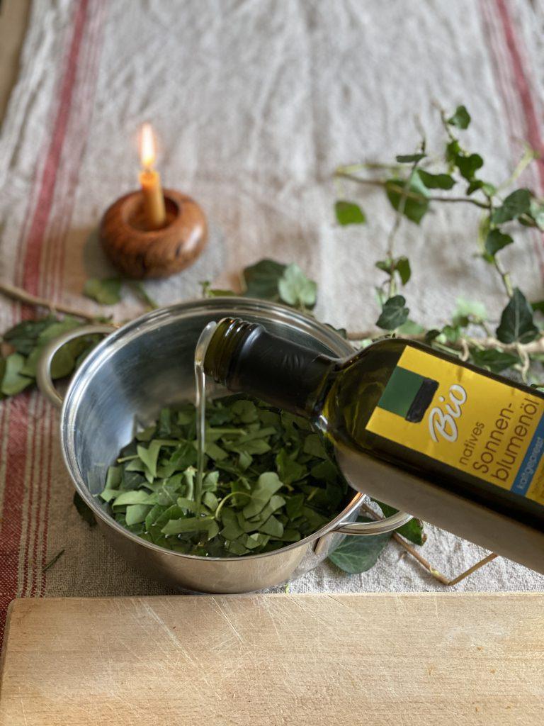 Bio-Sonnenblumenöl wird über Efeustückchen in Topf gegossen. Das ist die Grundlage zum Peeling selber machen.
