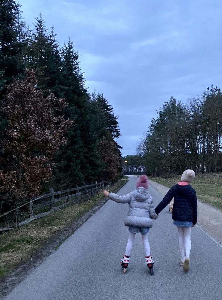 Große Schwester hält kleiner Schwester die Hand beim Inline-Fahren