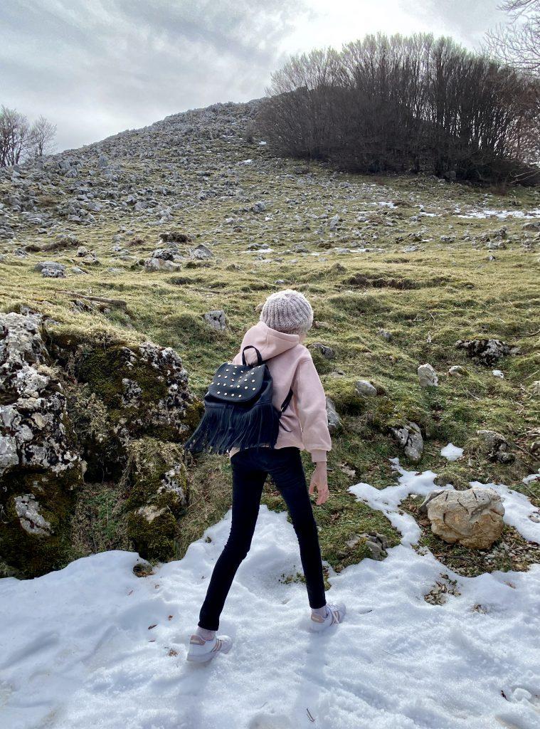 Kind auf Schnee vor Berg