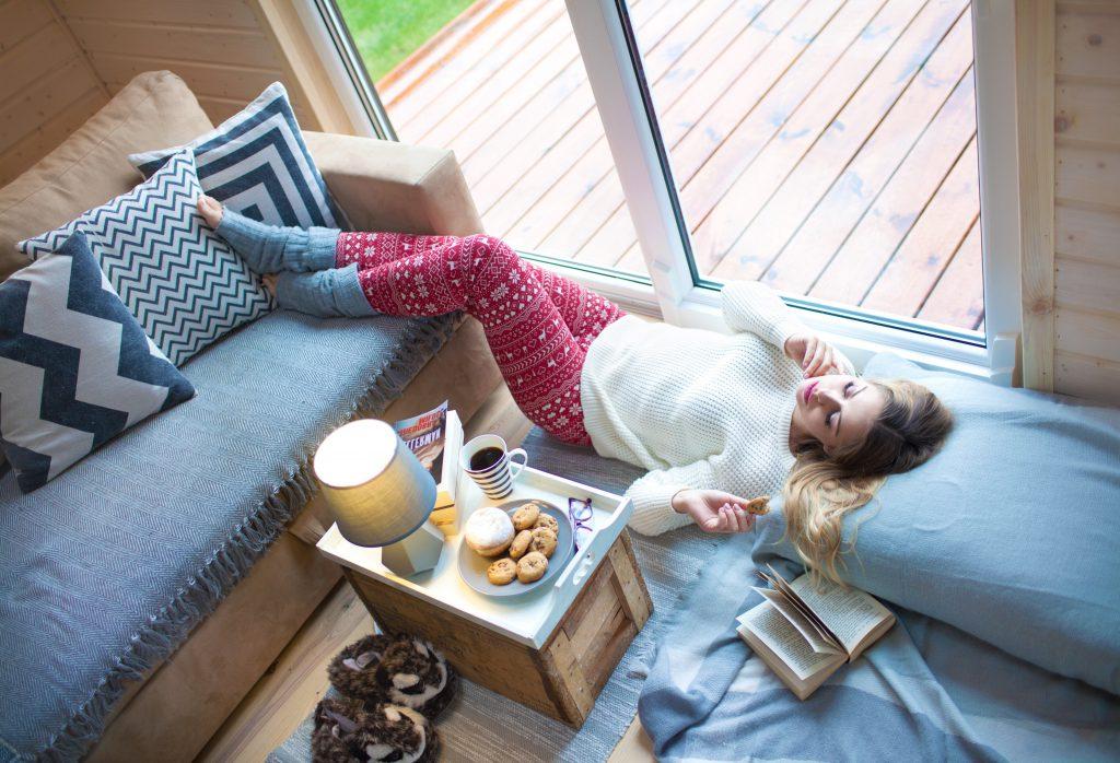 Frau liegt mit Wollsocken auf dem Sofa, neben sich Tee und Kekse. Auch Faulsein/Weniger machen ist eine schöne Fasten-Idee, besonders wenn man dazu neigt, sich immer zu viel vorzunehmen!