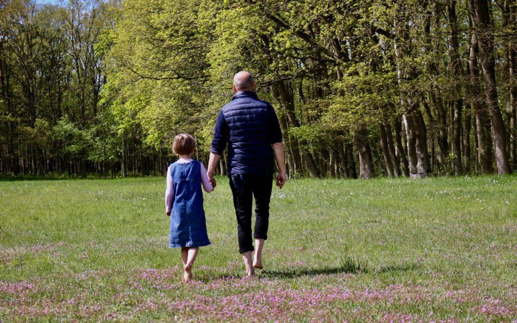 Eine von 18 Fasten-Ideen: Öfter mal spazieren gehen. Auf dem Bild geht ein Mann mit einem Kind auf einer Wiese entlang, die auf einen Wald zuführt.