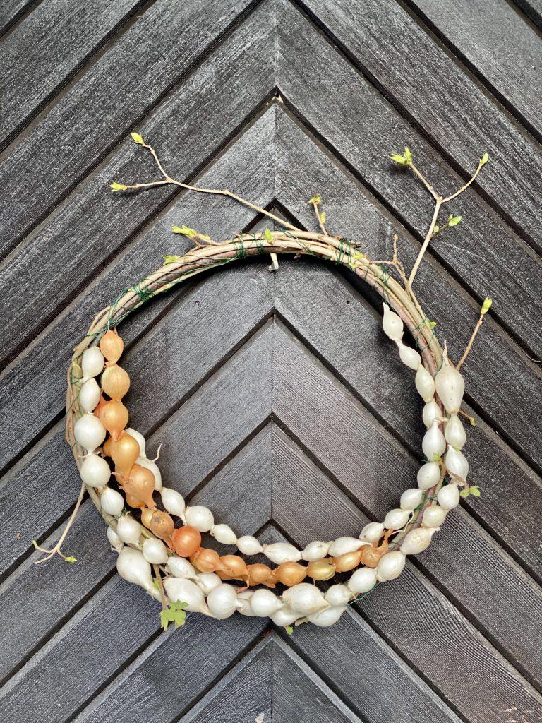 Dekoration mit Steckzwiebeln: Kranz aus Zweigen und mit Steckzwiebel-Ketten verziert, an Haustür hängend