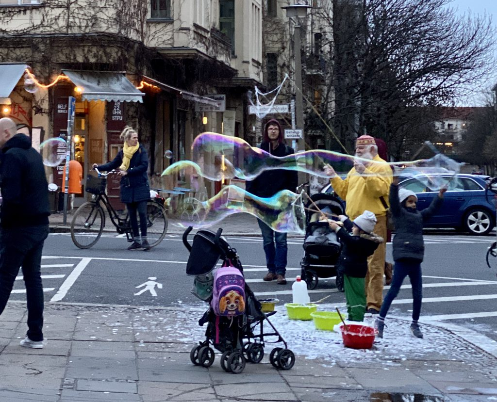 Seifenblasen-Macher und Spaziergänger auf Bürgersteig vor altem Haus in Berlin Prenzlauer Berg