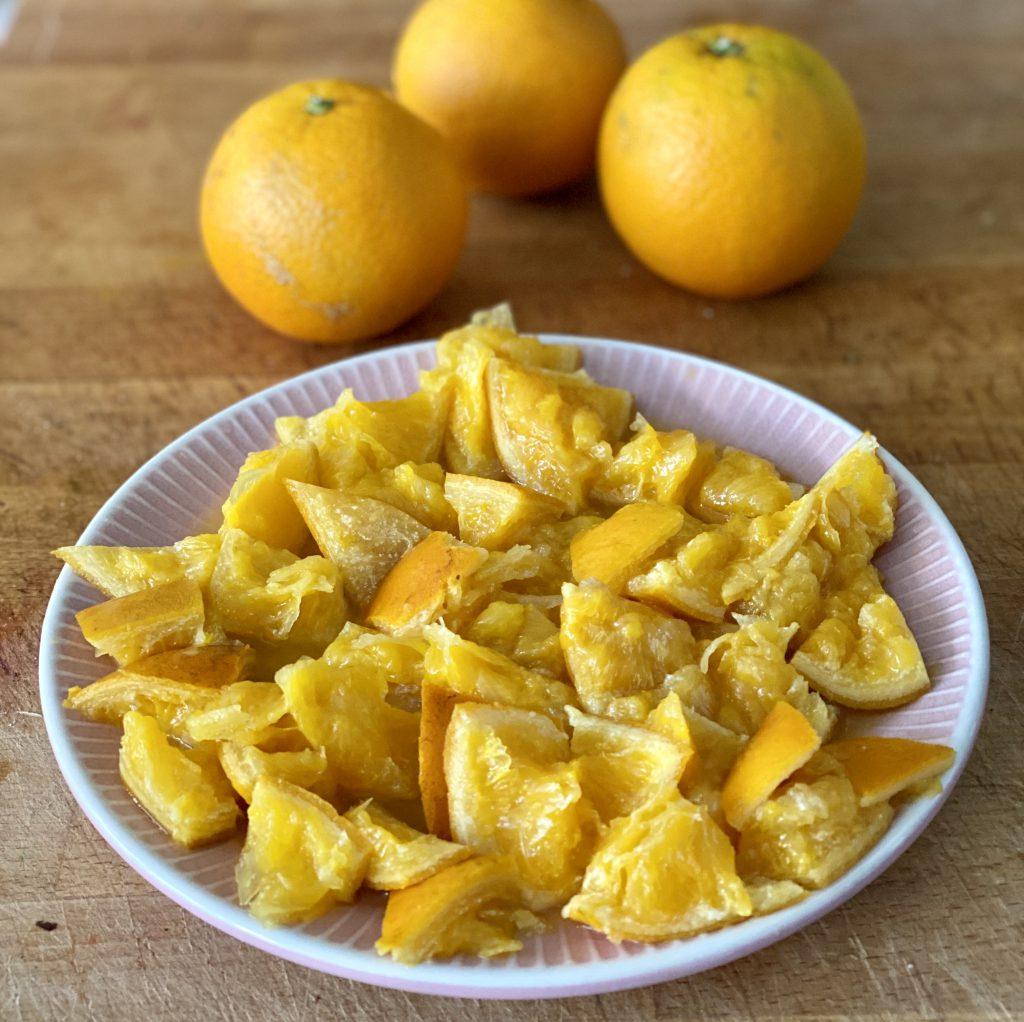 Den Orangen-Mandel-Kuchen aromatisiert man mit den klein geschnittenen, pürierten ganzen Orangen. Im Bild: Klein geschnittene Orangen auf rosa Teller.
