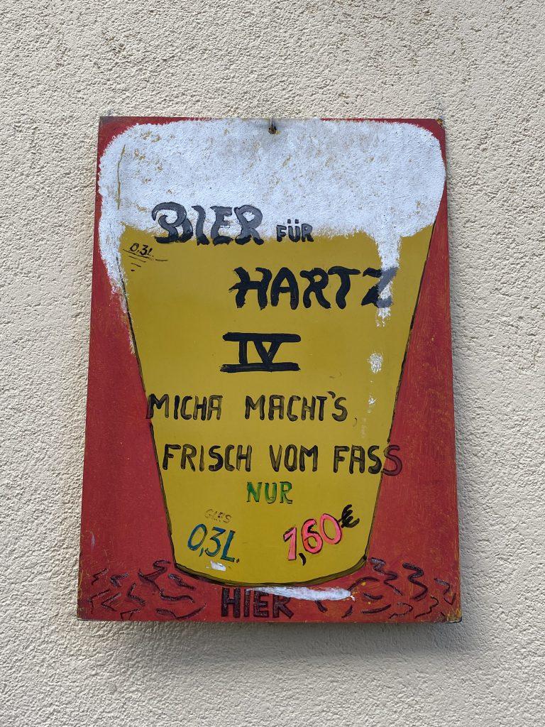 """Ein perfekter Tag in Berlin ist für manche an Bier gekoppelt: Spruch-Tafel: """"Bier für Hartz 4 - Micha macht's- Frisch vom Fass - 0,3 l nur 1,60"""