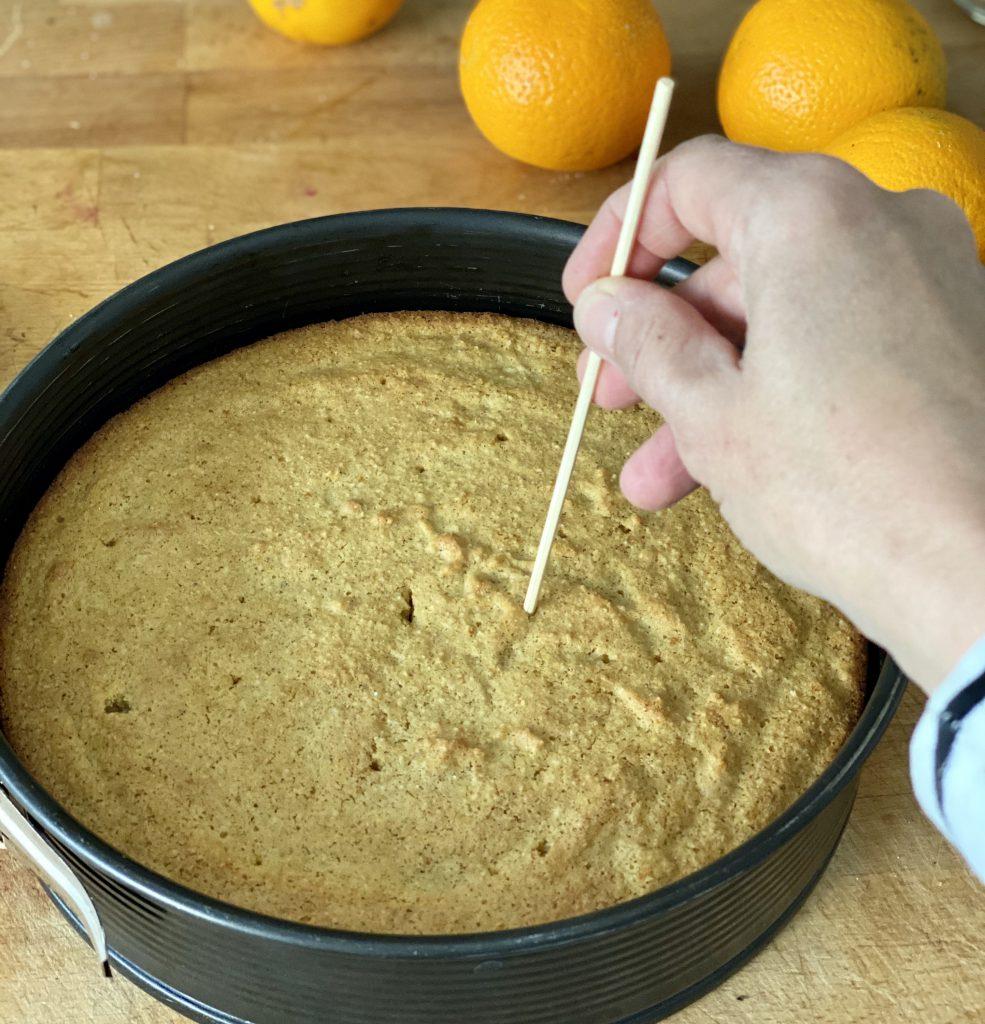 Ein Schaschlikspieß sticht Löcher in die Oberfläche des Orangen-Mandel-Kuchens.