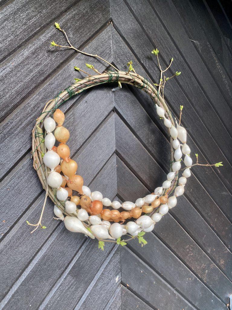 Dekoration mit Steckzwiebeln: Kranz aus Zweigen und Ketten kleiner Steckzwiebeln in weiß und gelb