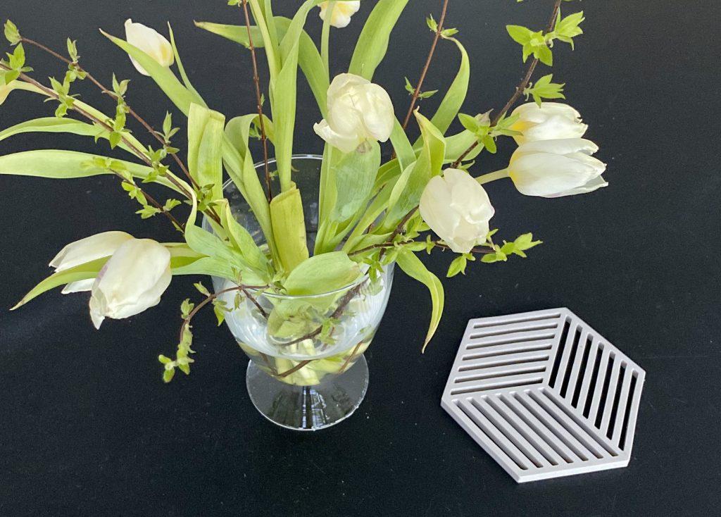 Blumenstrauß auf Tisch, daneben Topfuntersetzer mit Geometrie-Form