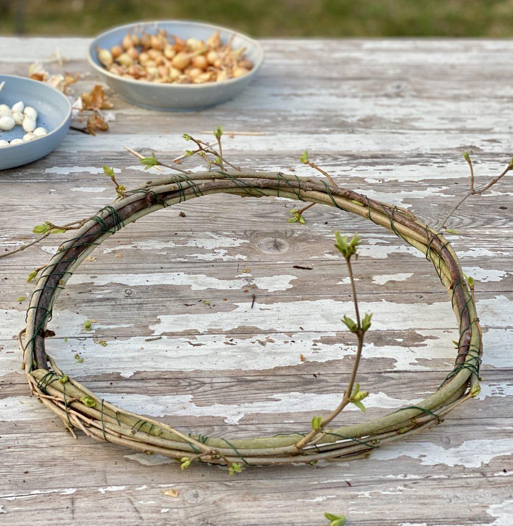 Kranz aus Zweigen und mit Steckzwiebel-Ketten verziert, auf Gartentisch liegend