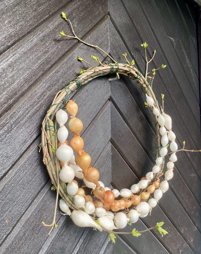 Dekoration mit Steckzwiebeln: Kranz aus Zweigen und mit Steckzwiebel-Ketten verziert, an Haustür gehängt