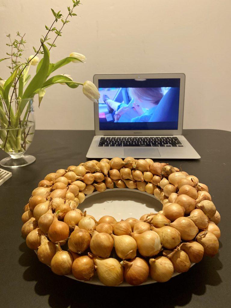 Zwiebelkranz vor Laptop mit Film auf schwarzem Tisch