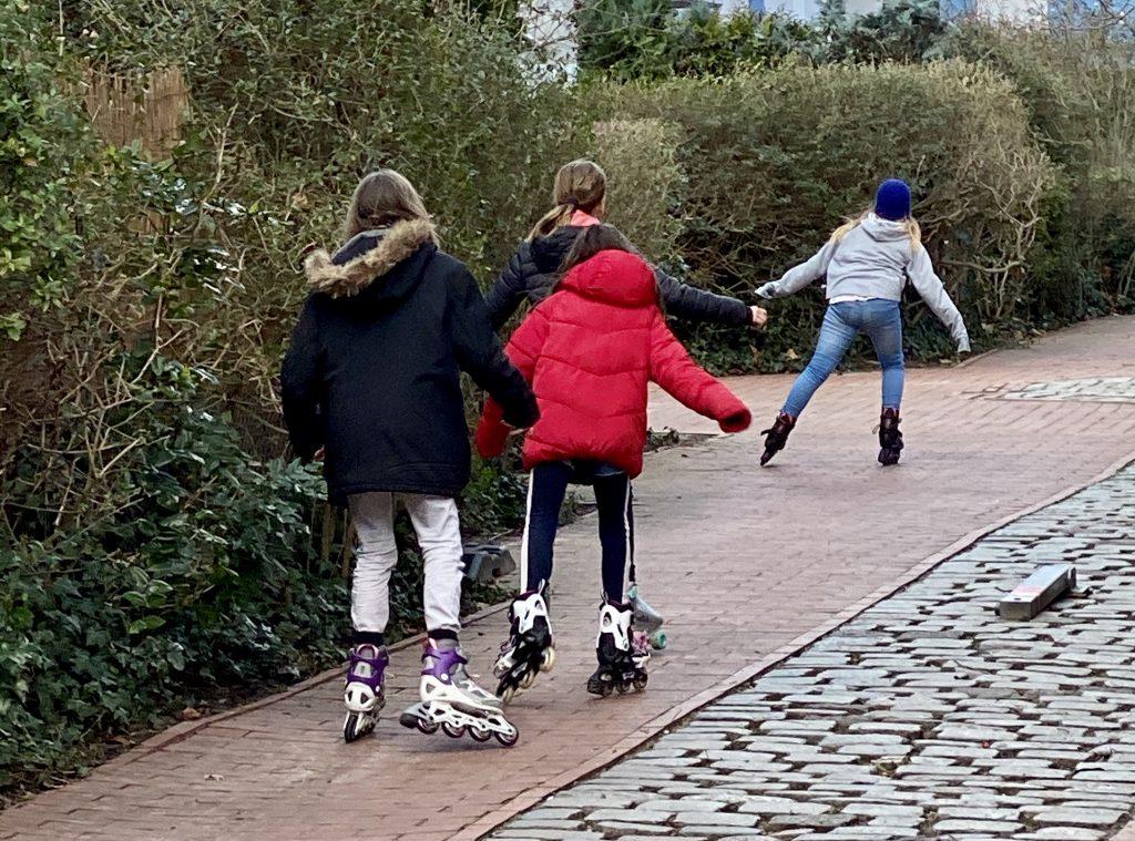 Vier Mädchen fahren Inliner zwischen Gebüschen