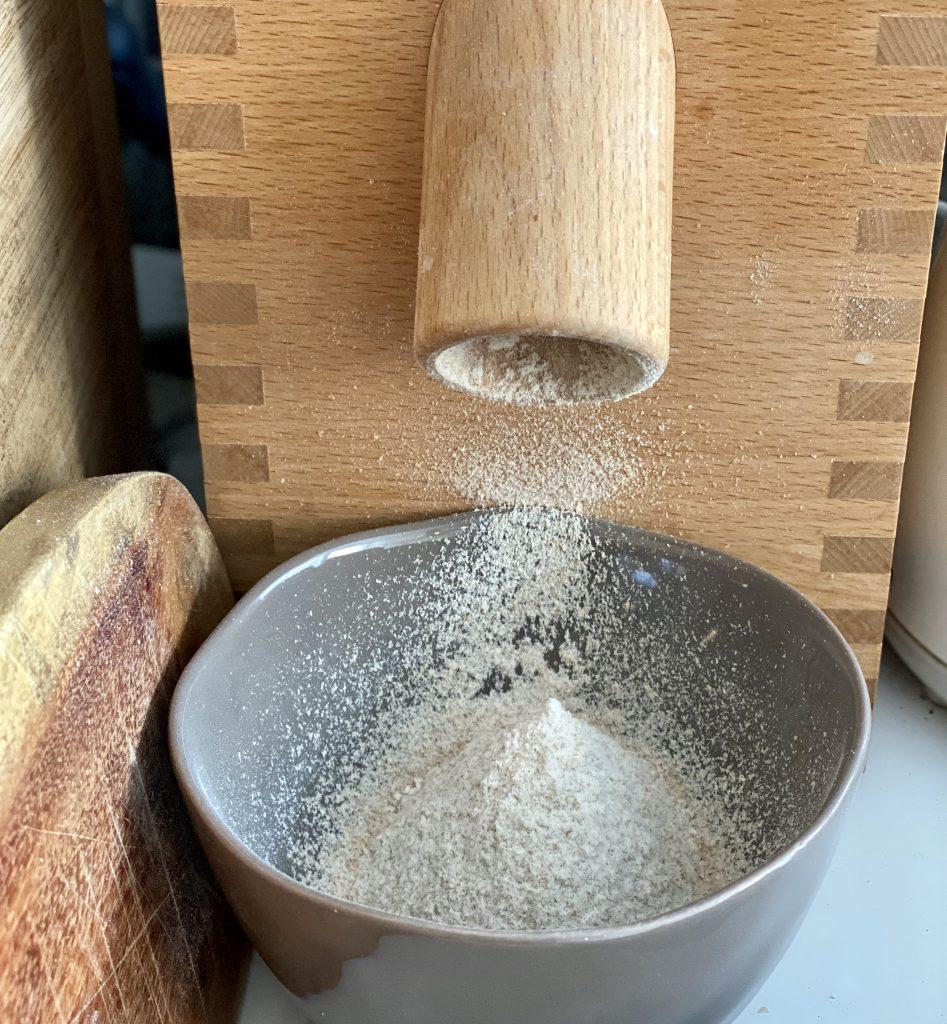 In den Orangen-Mandel-Kuchenkommt nur ganz wenig Mehl. Hier: Mehl wird mit Holz-Getreidemühle frisch gemahlen.
