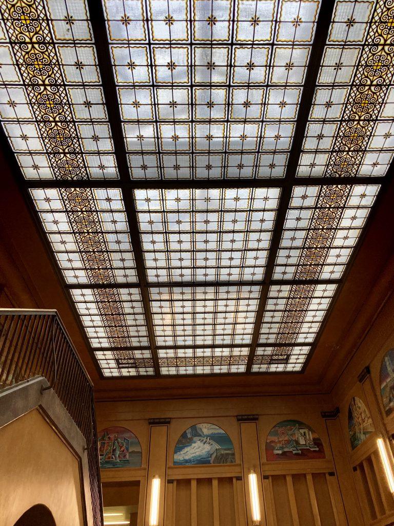 Ein perfekter Tag in Berlin kann Dich auch ins Stadtbad Neukölln führen: Die gläserne Decke in der Eingangshalle ist sehr schön