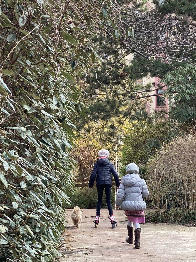 2 Kinder mit Inlinern zwischen Bäumen und Gebüsch