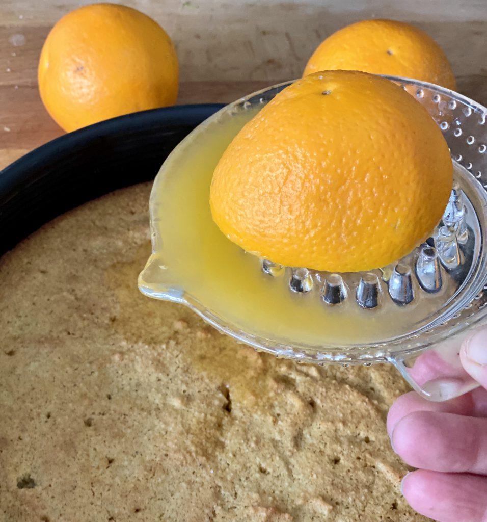 Eine Zitruspresse mit ausgepresster Orange darauf gießt Orangensaft auf den Kuchen.