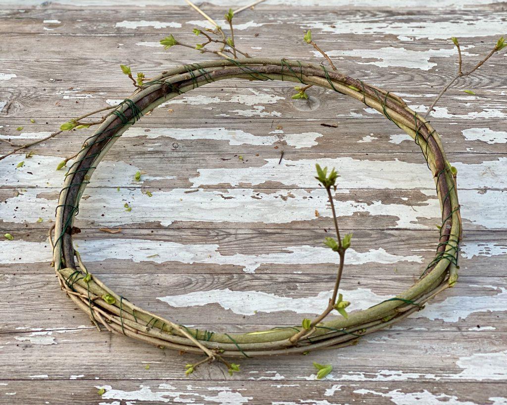 Dekoration mit Steckzwiebeln: Kranz aus Zweigen und mit Steckzwiebel-Ketten verziert, auf Gartentisch liegend