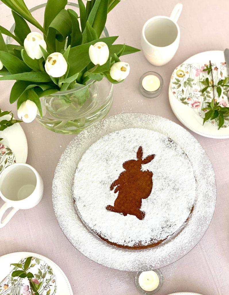 Sizilianischer Orangen-Mandel-Kuchen auf Ostertafel: rosa Tischdecke, weiße Teller mit Blumenservietten, weiße Tulpen in Vase.