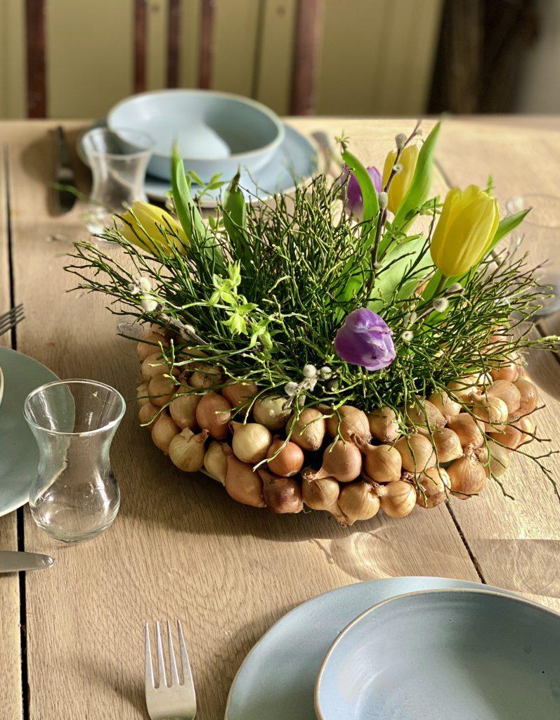 Dekoration mit Steckzwiebeln: dicker Kranz mit gelben Steckzwiebeln und  Blaubeerkraut auf Esstisch aus heller Eiche