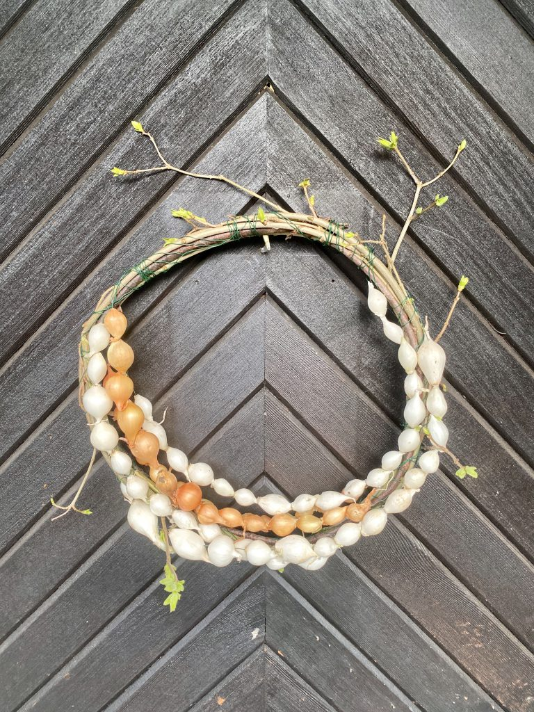 Kranz aus Zweigen und mit Steckzwiebel-Ketten verziert, an Haustür aufgehängt