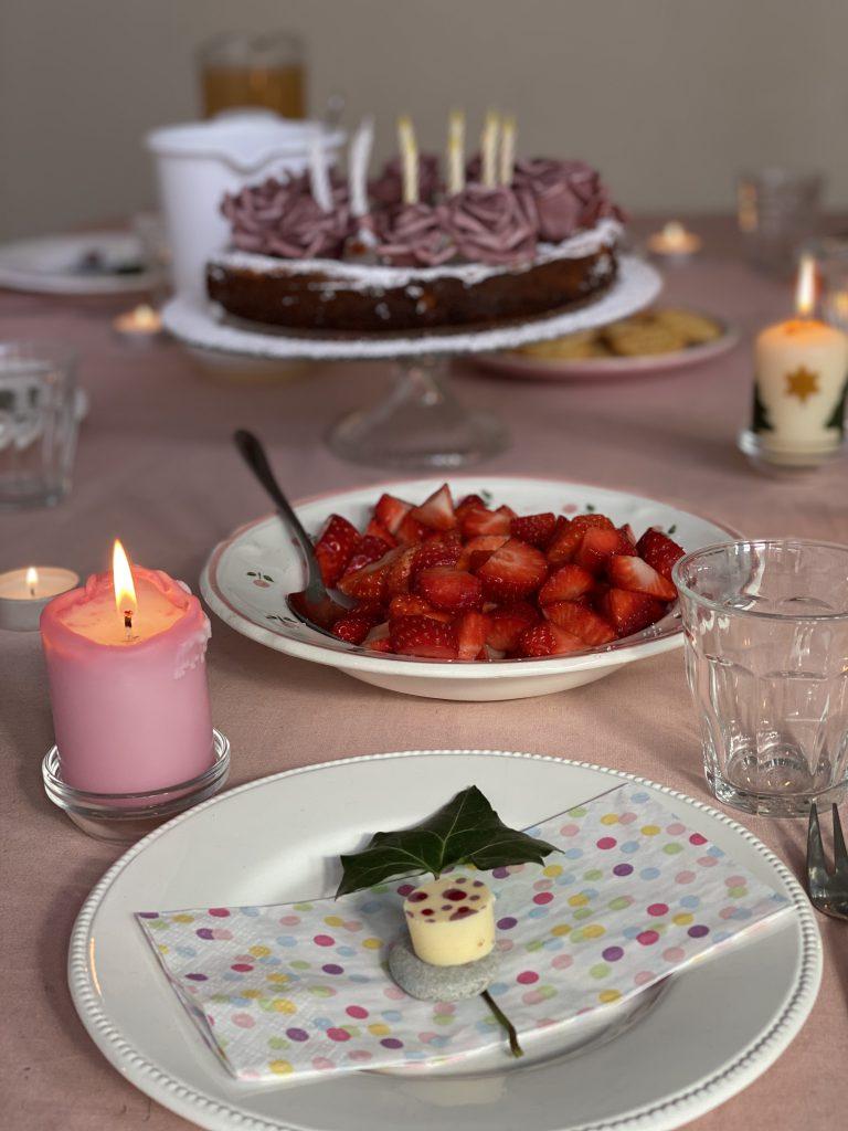Geburtstagstisch mit Torte, Kerzen und Erdbeeren