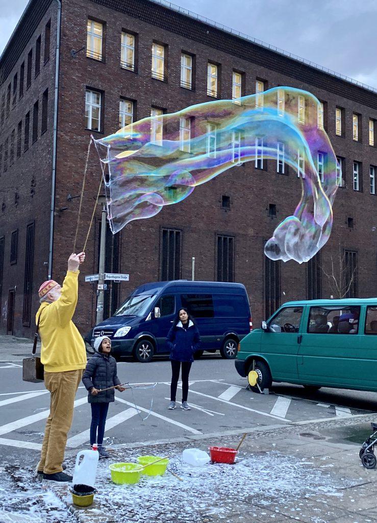 Seifenblasen-Macher und Kinder vor altem Gebäude