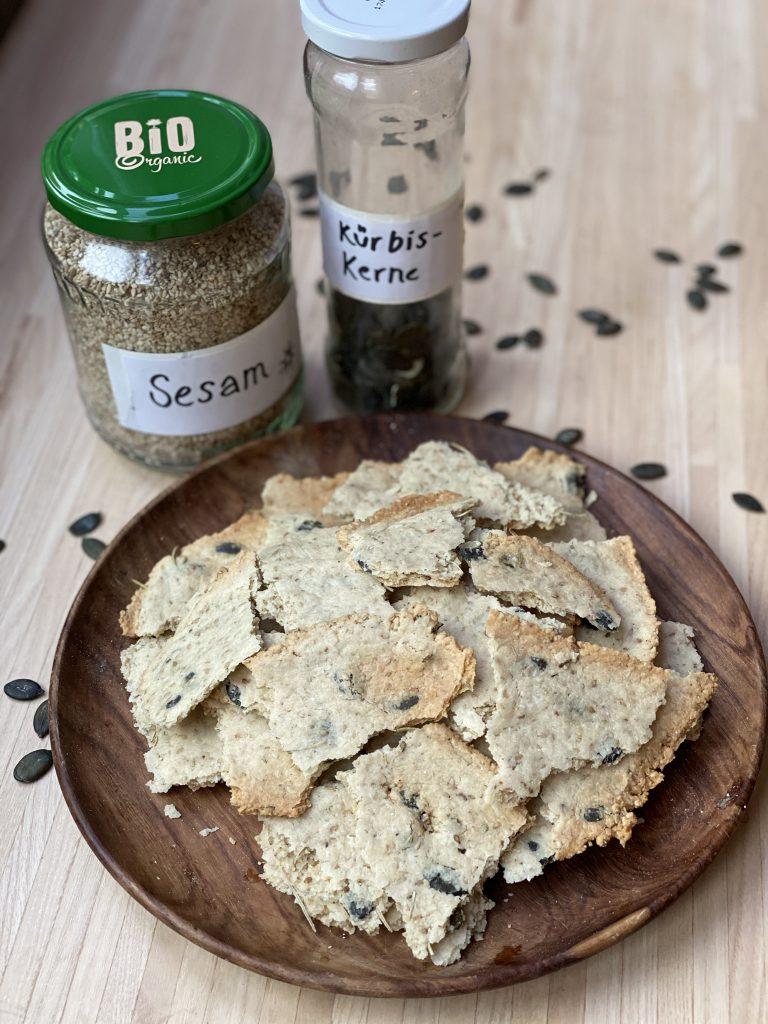Teller mit Paleo-Crackern, dahinter Schraubgläser mit Sesam und Kürbiskernen