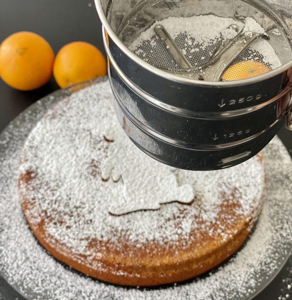 fast überall auf dem Orangen-Mandel-Kuchen ist nun Puderzucker