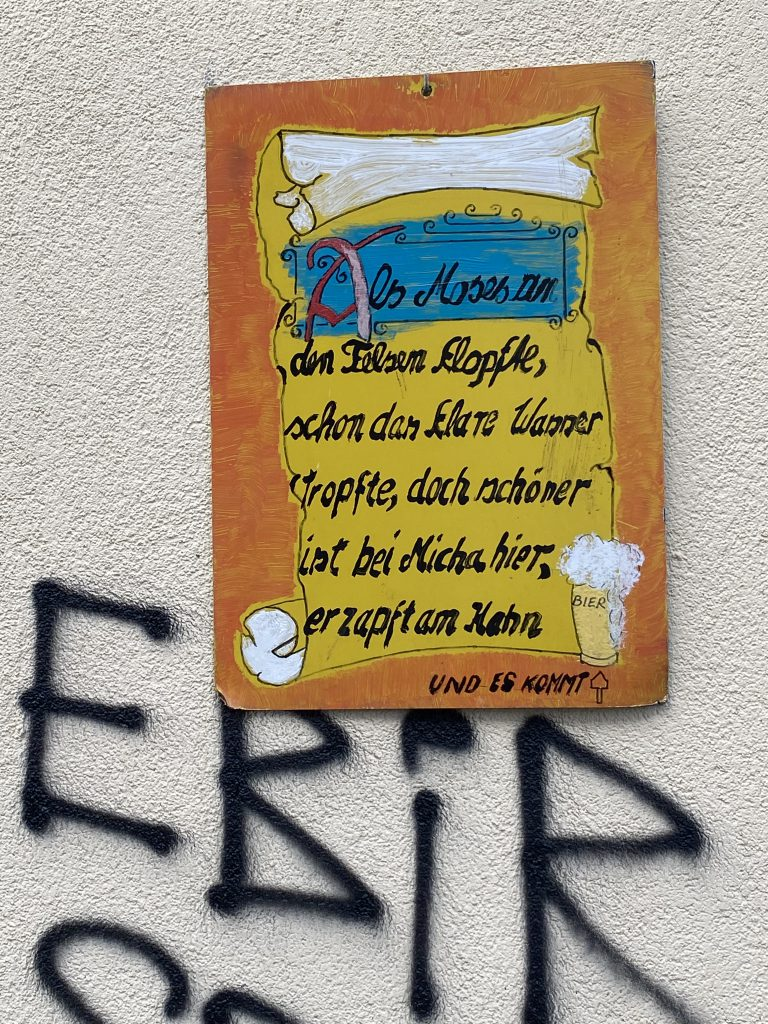 """Ein perfekter Tag in Berlin ist für manche an Bier gekoppelt: Spruch-Tafel an Hauswand: """"Als Moses an den Felsen klopfte, schon das klare wasser tropfte. Doch schöner ist's bei Micha hier, er zapft am Krug und es kommt Bier."""" Darunter vier Graffiti-Buchstaben: EBIR"""