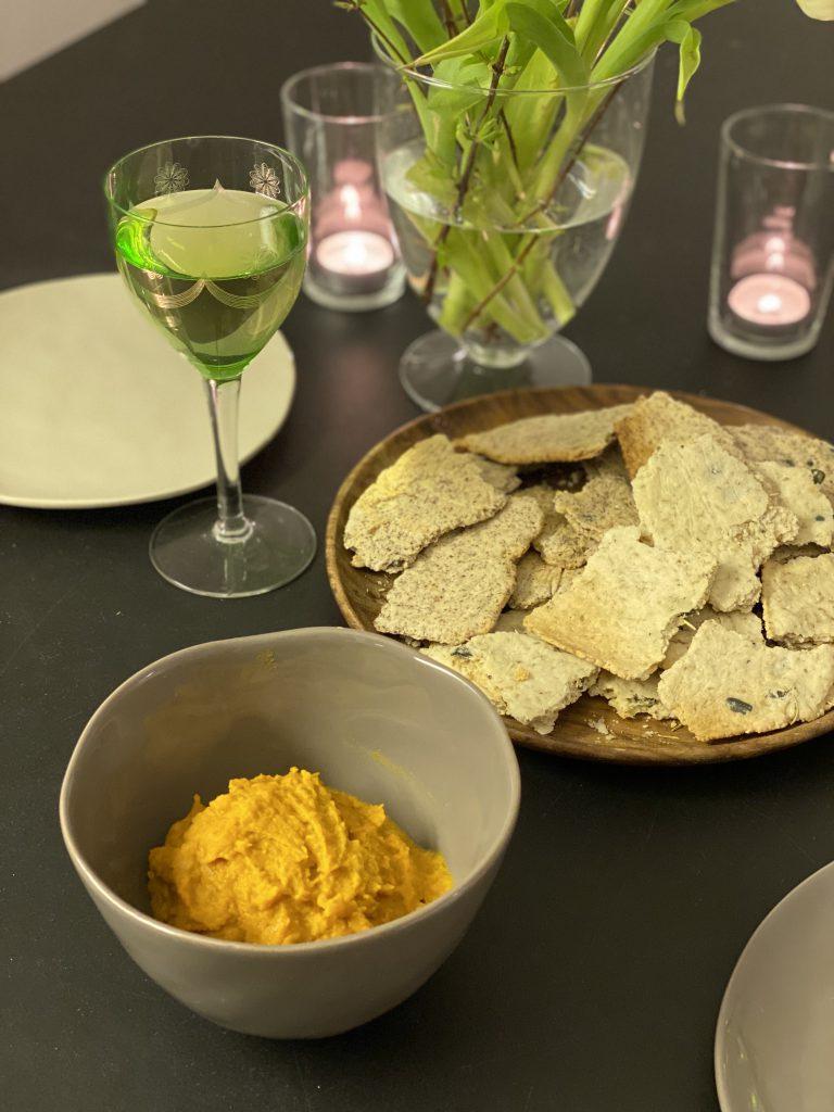 Tisch mit Teller mit Paleo-Crackern, Schale mit Dip, Blumen, Kerzen und gefülltem Weinglas