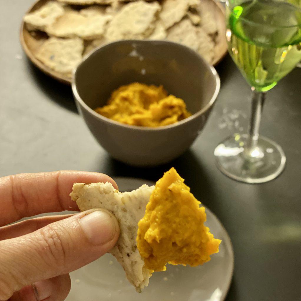 Paleo-Cracker in Hand, mit Dip drauf, vor Weinglas, Schale mit Dip und Teller mit Crackern