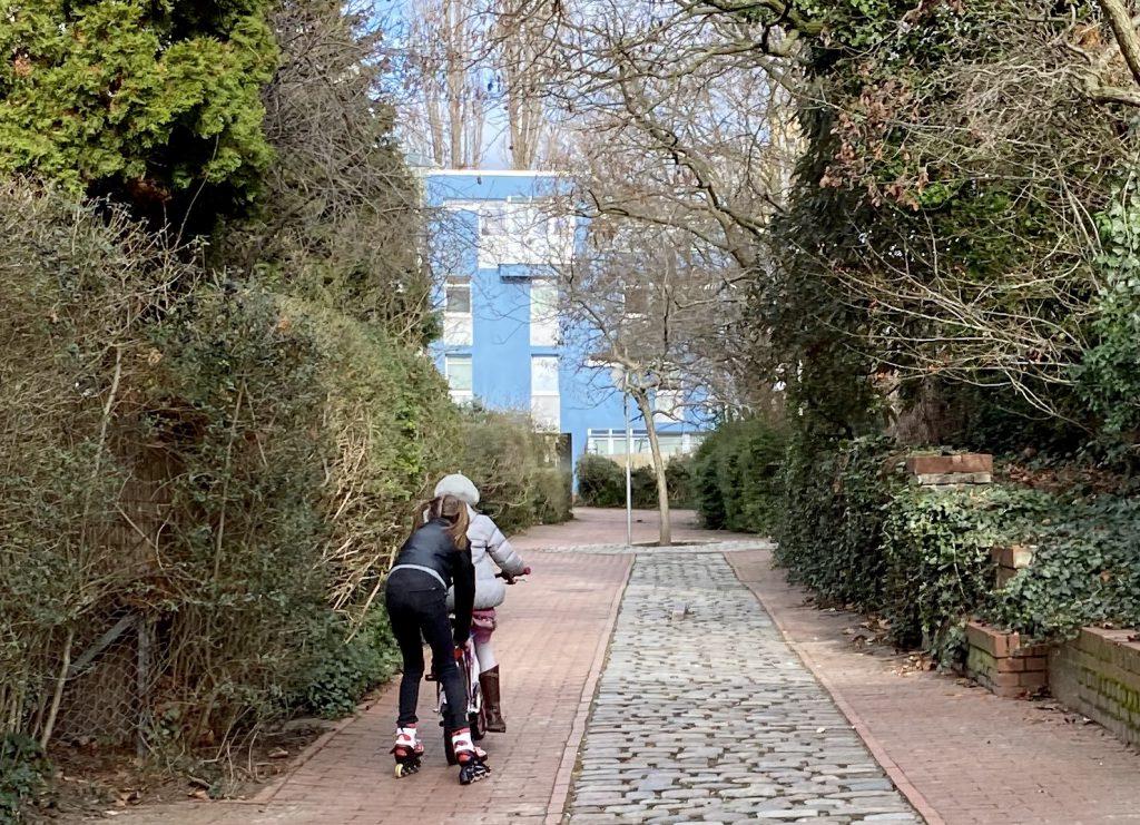 Kinder mit Fahrrad und Inlinern zwischen Büschen und Bäumen