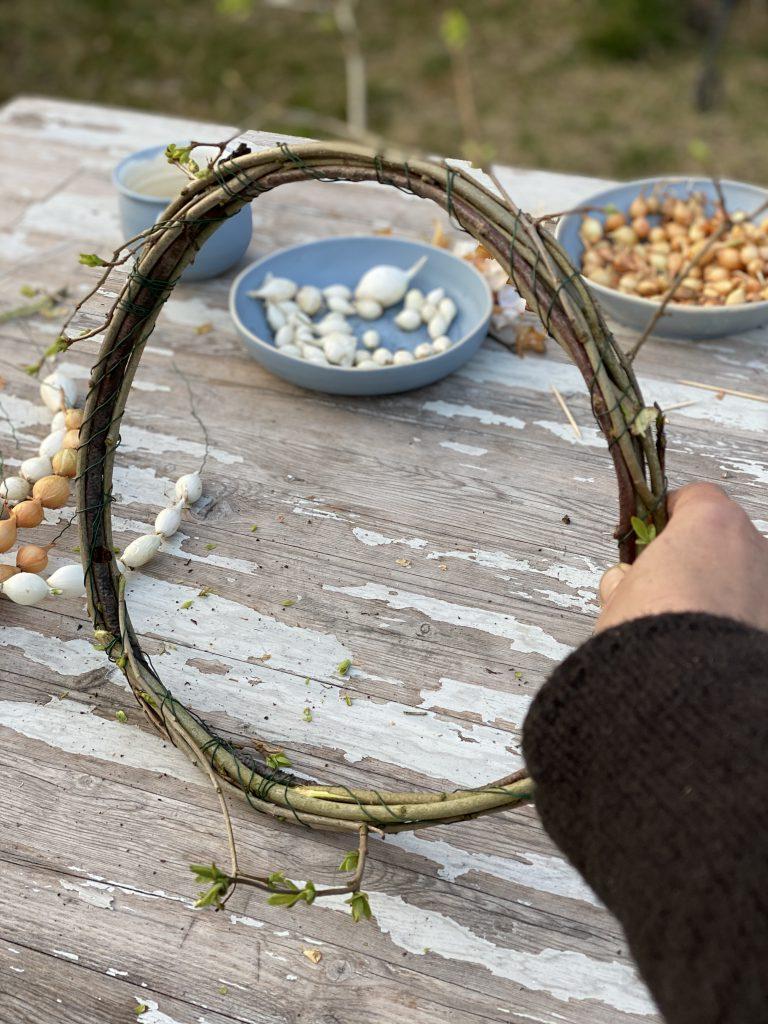 Dekoration mit Steckzwiebeln: Kranz aus Zweigen und mit Steckzwiebel-Ketten verziert, vertikal stehend auf Gartentisch