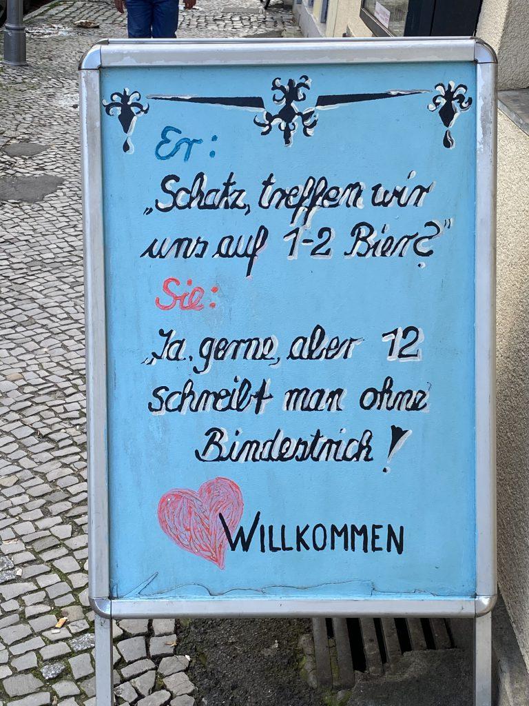 """Ein perfekter Tag in Berlin ist für manche an Bier gekoppelt: Spruch-Tafel: """"Er: """"Schatz, treffen wir uns auf 1-2 Bier?"""" Sie: """"Ja, gerne, aber 12 schreibt man ohne Bindestrich!"""""""