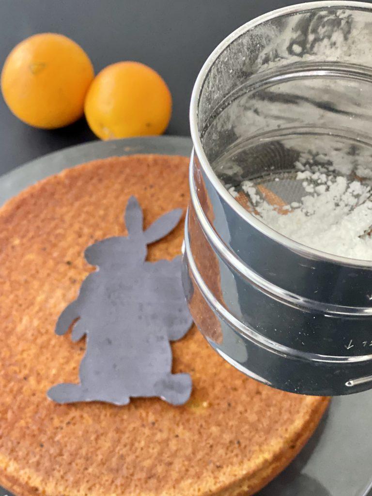 umgedrehter Kuchen mit hasen-Form drauf, Sieb mit Puderzucker darin.
