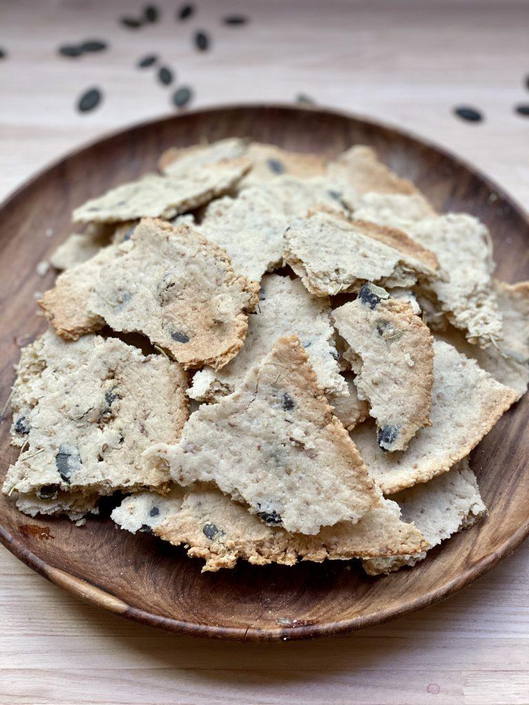 Tller mit Paleo-Cracker und Kürbiskernen auf dem Tisch verstreut