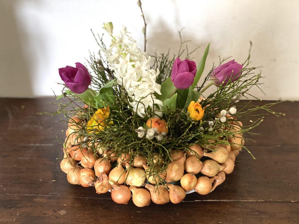 Dekoration mit Steckzwiebeln: dicker Kranz mit Blaubeerkraut, Hyazinthen, Ranunkeln und Tulpen