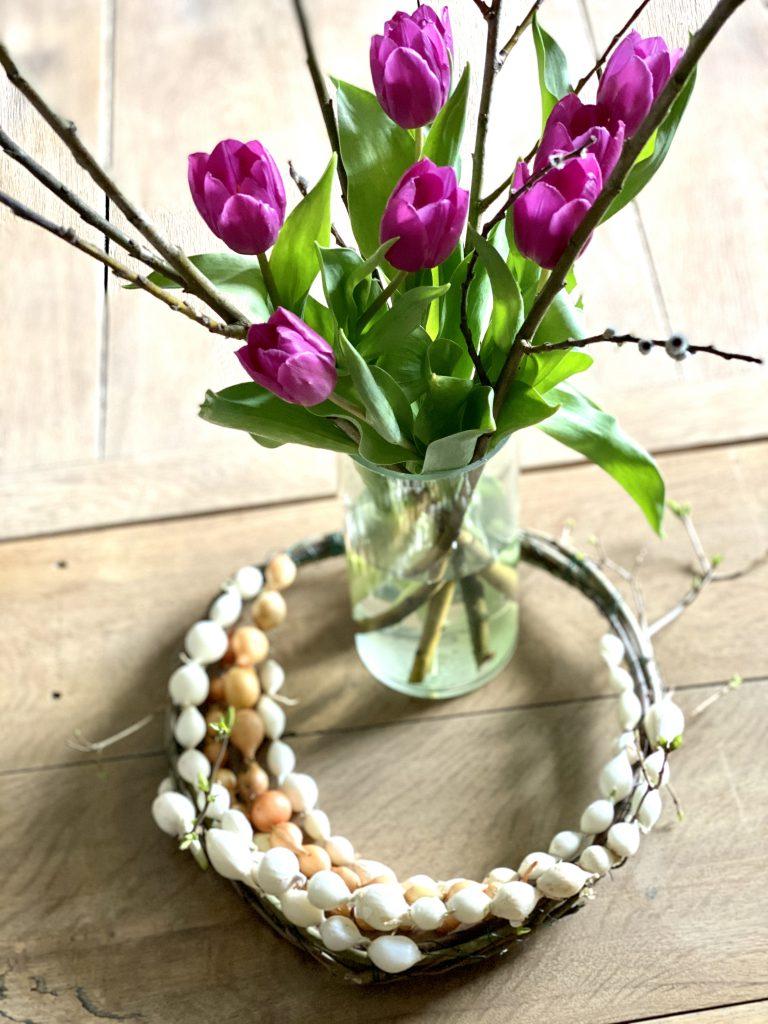 Dekoration mit Steckzwiebeln: Tulpenstrauß mit Weidenkätzchen auf Tisch, Zwiebelkranz um die Vase