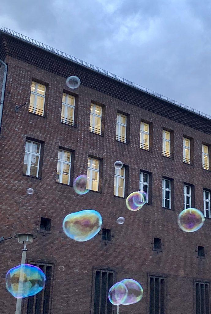 großes altes Gebäude mit Riesen-Seifenblasen davor