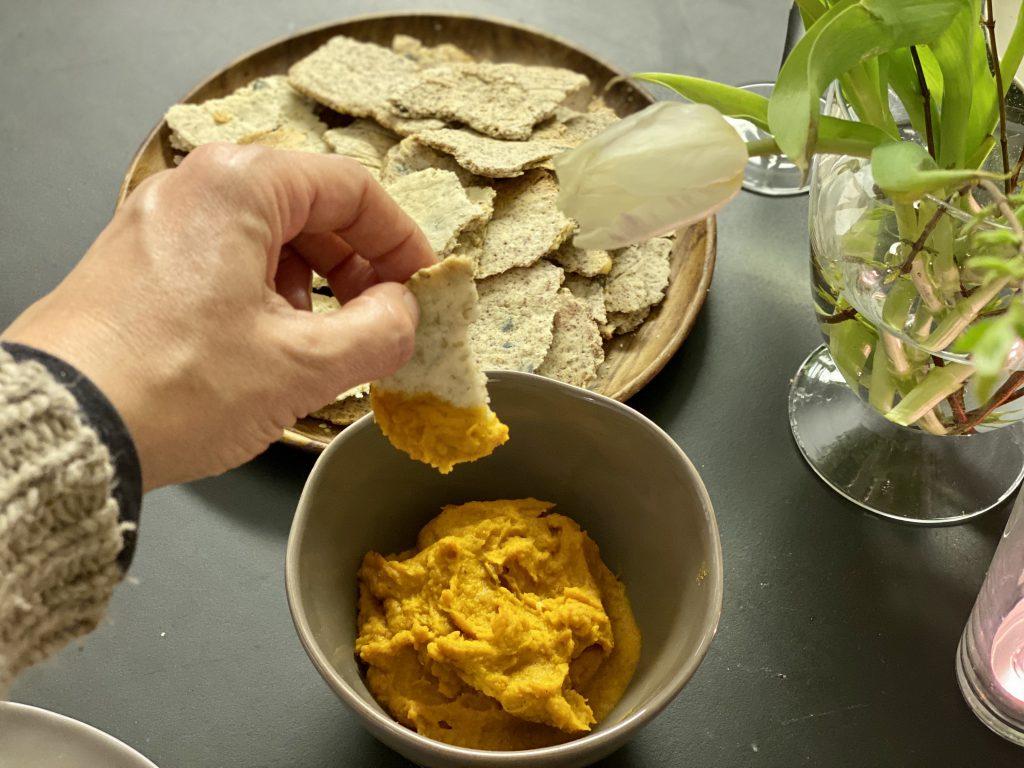 Tisch mit Teller mit Paleo-Crackern, Schale mit Dip, Hand taucht Paleo-Cracker in Dip